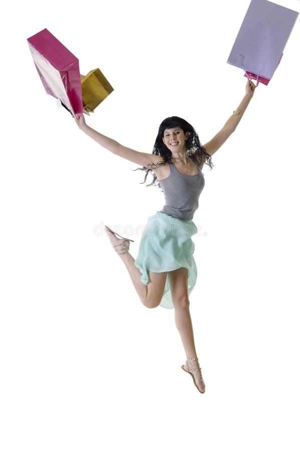 Młody piękny kobiety doskakiwanie dla radości z jej nowymi zakupami zdjęcie stock
