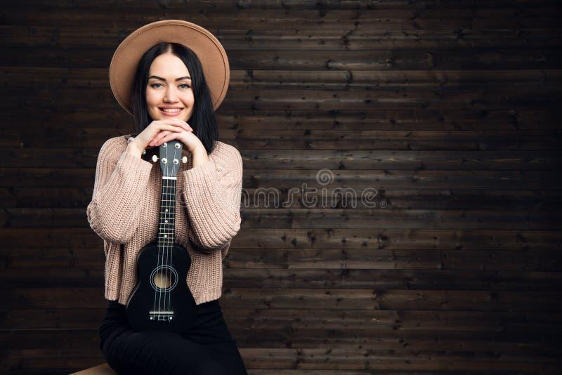 Młody piękny kobiety obsiadanie na krześle jest ubranym kapelusz z ukulele Dziewczyna z rękami składał na małej gitarze na zmroku obraz royalty free