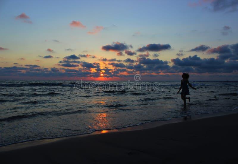 Młody piękny kobiety odprowadzenie wzdłuż plaży przy morzem w wieczór zdjęcia stock