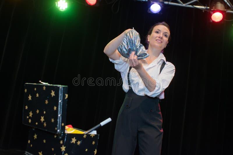 Młody piękny magik na scenie podczas przedstawienia obraz stock