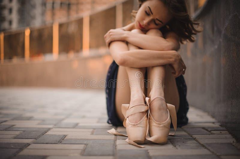 Młody piękny nowożytny stylowy baletniczego tancerza obsiadanie na ziemi w czerni sukni Selekcyjna ostrość zdjęcie stock