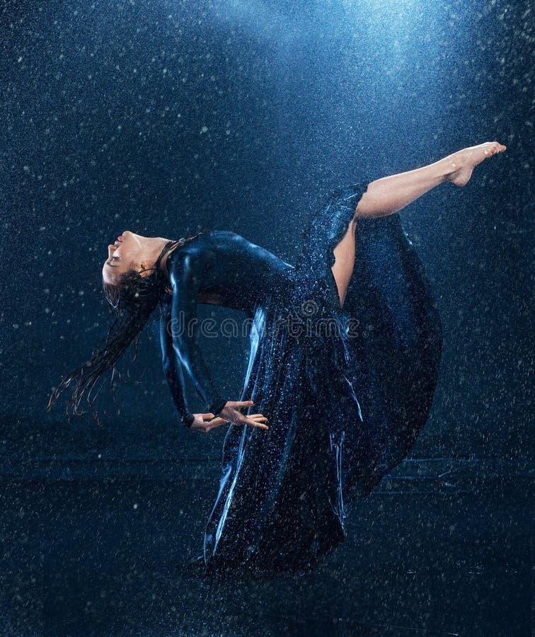 Młody piękny nowożytny tancerza taniec pod wodnymi kroplami zdjęcie stock