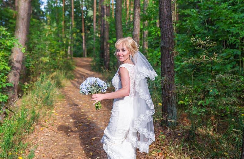 Młody piękny panna młoda spacer w zielonym lesie z bridal bukietem w białej ślubnej sukni obraz royalty free