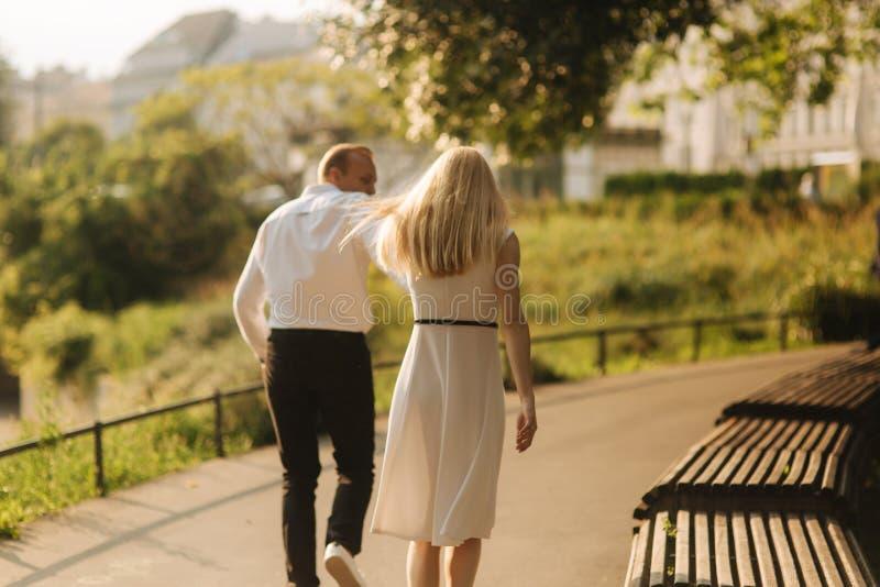 Młody piękny para mąż w białej koszula i kobiecie w smokingowym odprowadzeniu wokoło parka w lato czasie obrazy royalty free