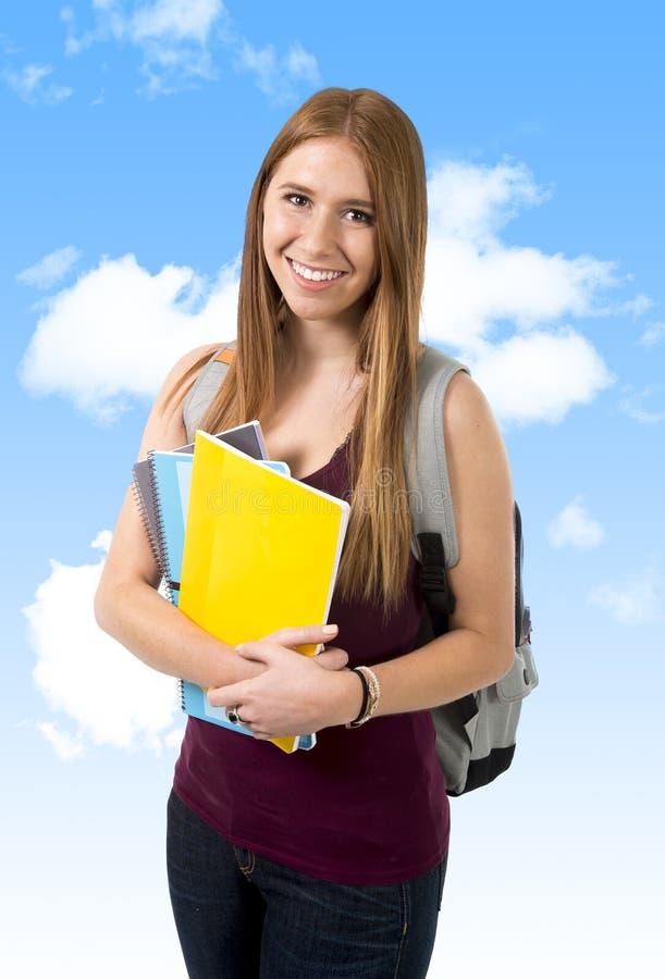 Młody piękny student collegu dziewczyny przewożenia plecak i książki pod niebieskim niebem zdjęcia stock