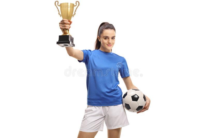 Młody piłkarz trzymający puchar na złoto obraz royalty free