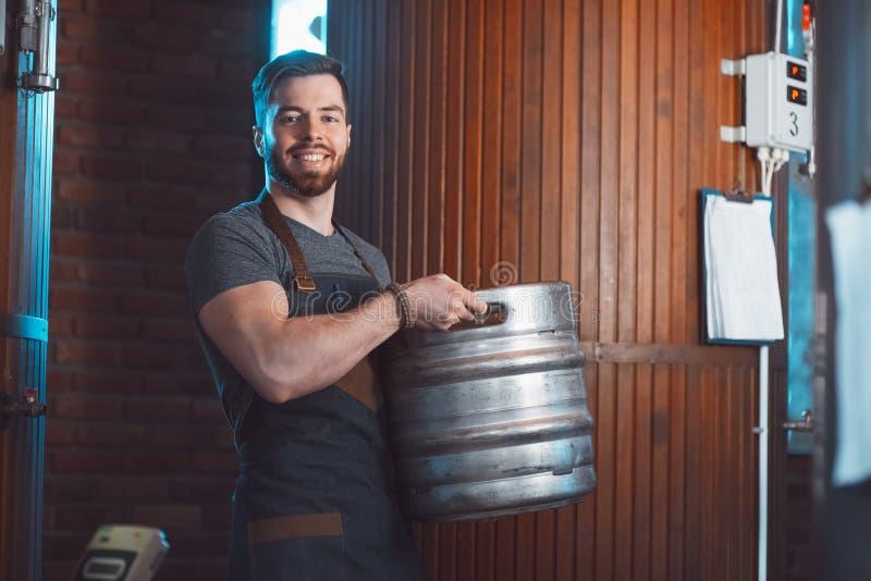 Młody piwowar w fartuchu trzyma baryłkę z piwem w rękach obrazy stock