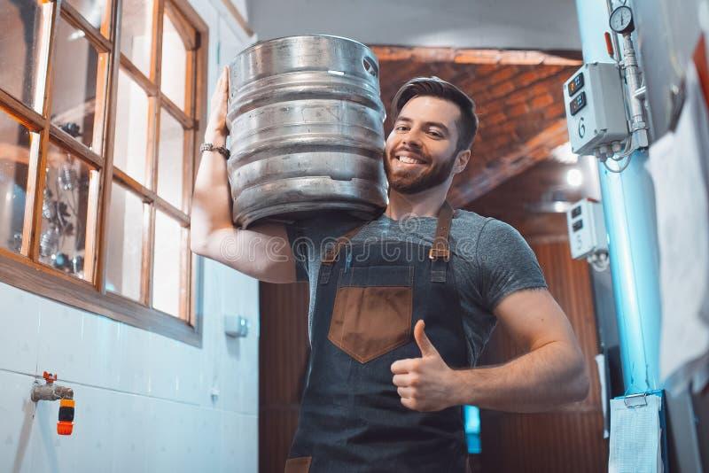 Młody piwowar w fartuchu trzyma baryłkę z piwem w rękach fotografia royalty free