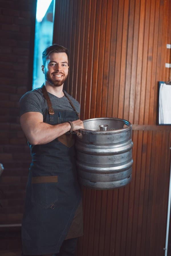 Młody piwowar w fartuchu trzyma baryłkę z piwem w rękach obrazy royalty free