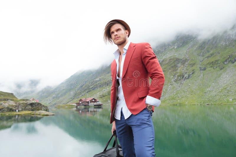 Młody podróżnik blisko halnego jeziora z kabiną zdjęcia stock