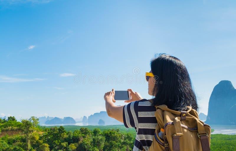 Młody podróżnik kobiety backpacker use telefon komórkowy bierze fotografię zdjęcia stock