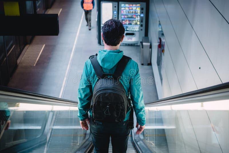 Młody podróżnika plecy widok w metro eskalatorze zdjęcie stock
