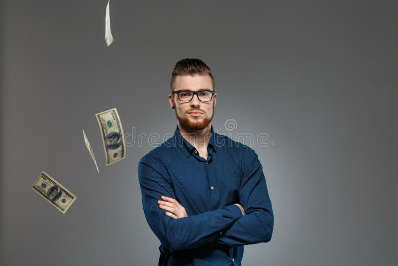 Młody pomyślny biznesmen pozuje wśród spada pieniądze nad ciemnym tłem obraz stock