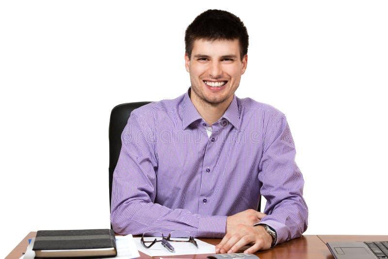 Młody pomyślny biznesmen pracuje przy jego biurkiem obrazy stock