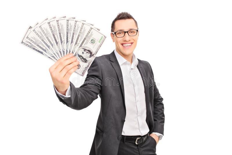 Młody pomyślny biznesmen trzyma stertę pieniądze fotografia royalty free