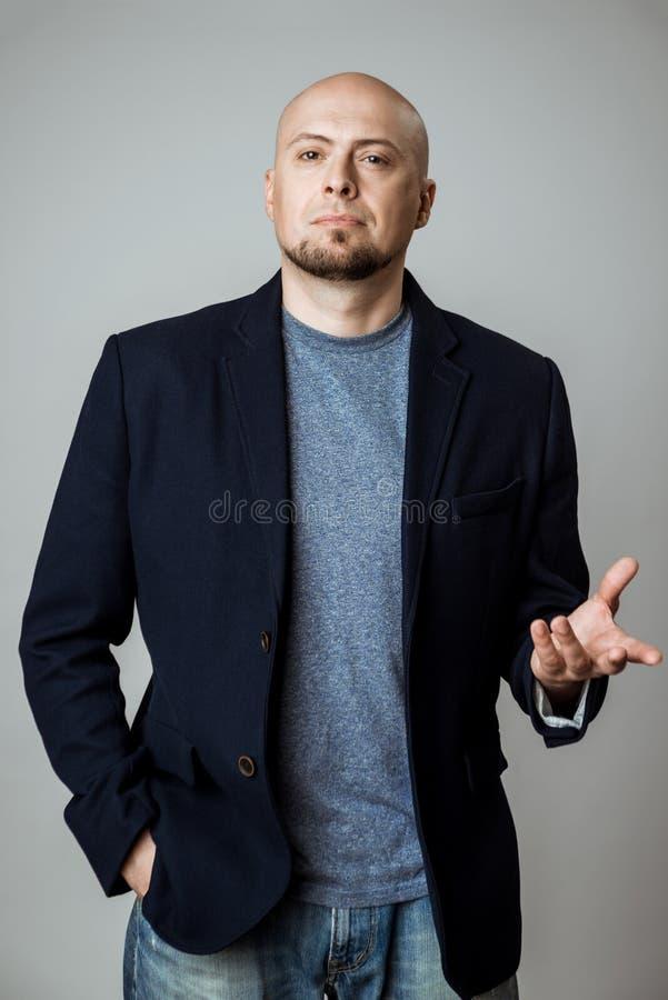 Młody pomyślny biznesmena główkowanie, pozuje nad beżowym tłem zdjęcie stock