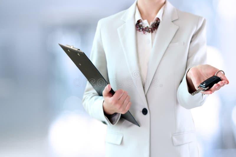 Młody pomyślny bizneswoman oferuje samochodowego klucz zdjęcia stock