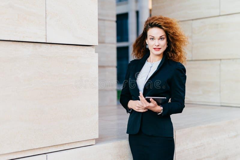 Młody pomyślny bizneswoman w eleganckich ubraniach, mieć luxuriant włosy, trzyma pastylkę w rękach podczas gdy iść dla pracy Wspa fotografia royalty free