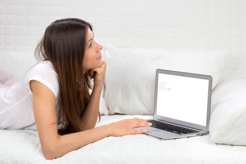 Młody pomyślny kobiety lying on the beach na kanapie z laptopem płaci rachunki zdjęcia royalty free