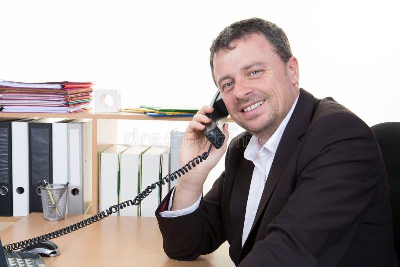 młody pomyślny mężczyzna jest ubranym kostium odzież opowiada na telefonie przy biurowym miejsca pracy biurkiem obrazy stock