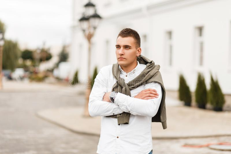 Młody pomyślny mężczyzna z ostrzyżeniem w białej koszula z zdjęcia royalty free