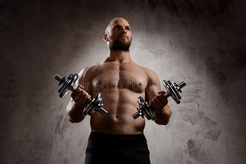 Młody potężny sportowa szkolenie z dumbbells nad ciemnym tłem obrazy royalty free