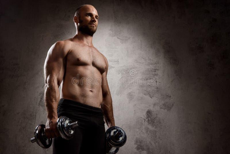 Młody potężny sportowa szkolenie z dumbbells nad ciemnym tłem fotografia royalty free