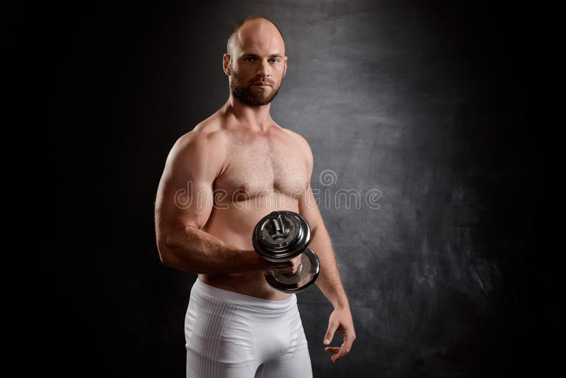 Młody potężny sportowa szkolenie z dumbbells nad czarnym tłem fotografia stock