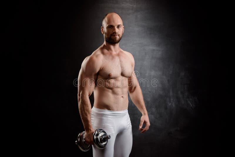 Młody potężny sportowa szkolenie z dumbbells nad czarnym tłem zdjęcie stock