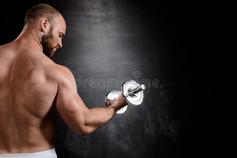 Młody potężny sportowa szkolenie z dumbbells nad czarnym tłem zdjęcia royalty free