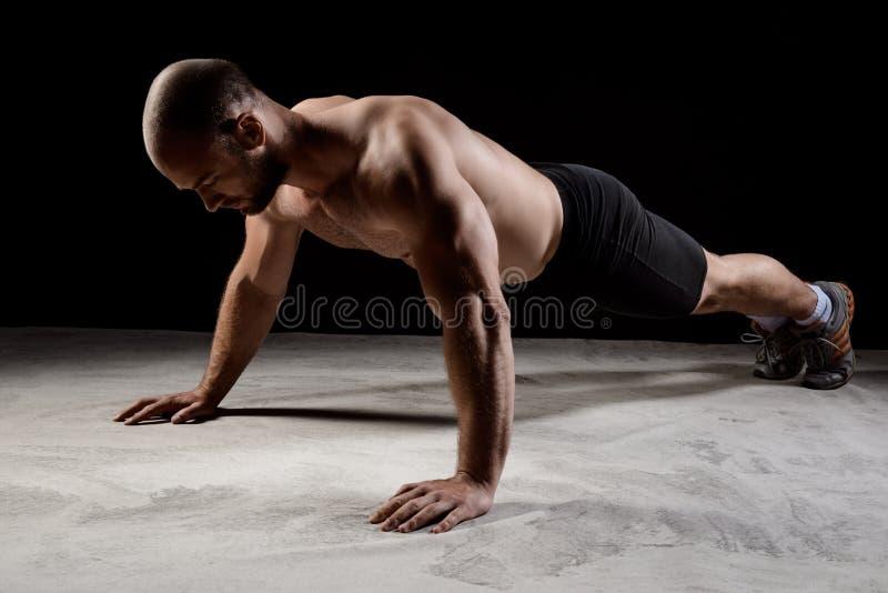 Młody potężny sportowiec podnosi nad ciemnym tłem szkolenie pcha zdjęcia royalty free