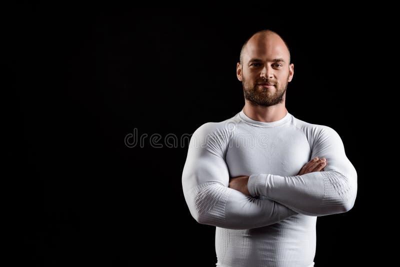 Młody potężny sportowiec w białej odzieży nad czarnym tłem zdjęcia royalty free