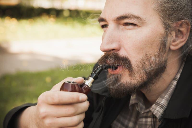 Młody poważny azjatykci brodaty mężczyzna dymi obraz royalty free