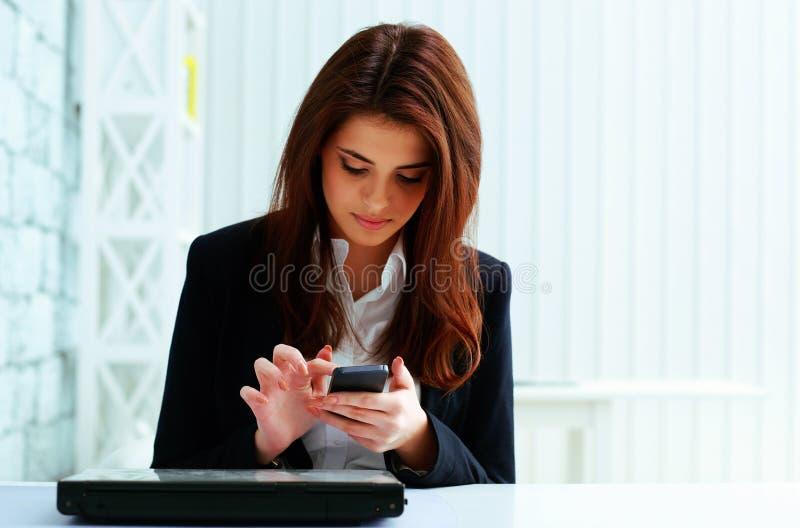 Młody poważny bizneswoman pisać na maszynie na jej smartphone zdjęcia royalty free