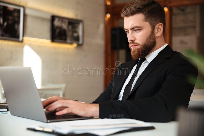Młody poważny brodaty biznesowy mężczyzna w czarnym kostiumu używać laptop wewnątrz zdjęcie royalty free