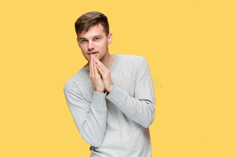 Młody poważny mężczyzna patrzeje ostrożnie i Mówi sekret obraz royalty free