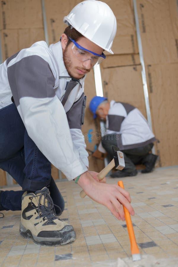Młody pracownik budowlany usuwa podłogowe płytki w łazience obrazy stock