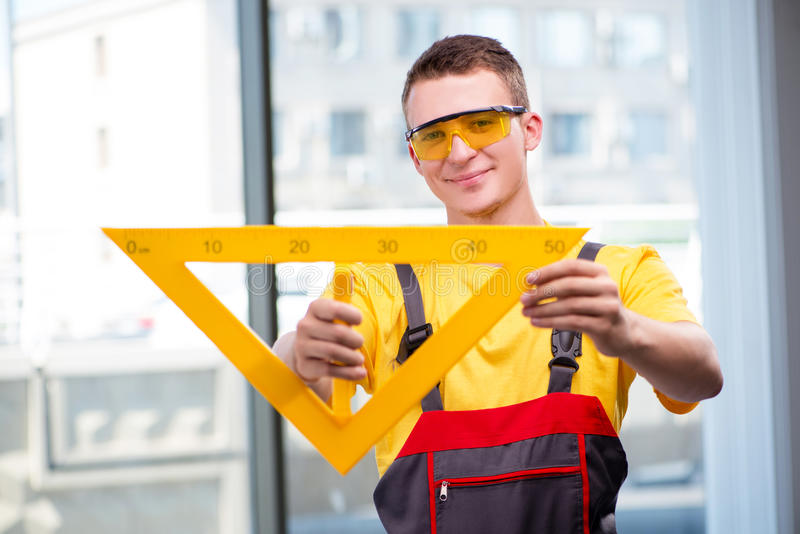 Młody pracownik budowlany w żółtych coveralls obrazy stock