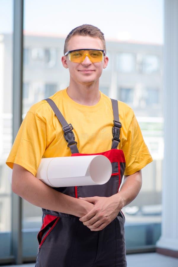 Młody pracownik budowlany w żółtych coveralls zdjęcia stock