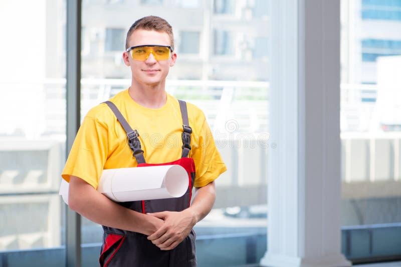 Młody pracownik budowlany w żółtych coveralls obrazy royalty free