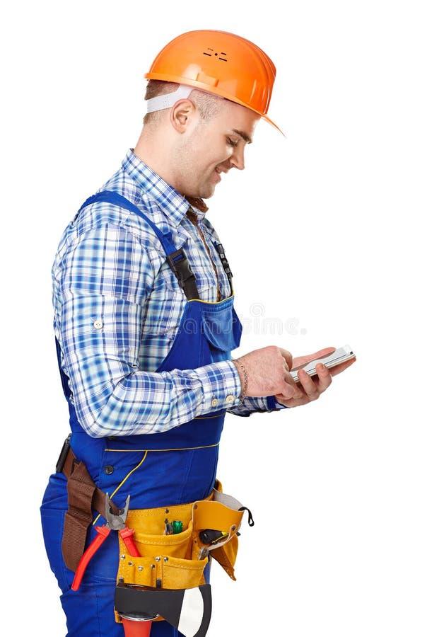 Młody pracownik budowlany z smartphone fotografia stock