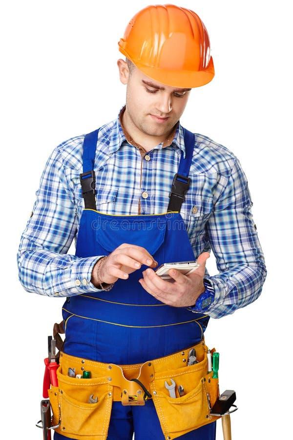 Młody pracownik budowlany z smartphone zdjęcie royalty free