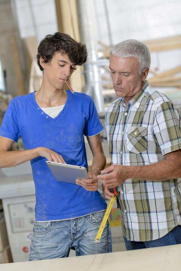 Młody pracownik pokazuje pastylkę starszy pracownik obrazy royalty free