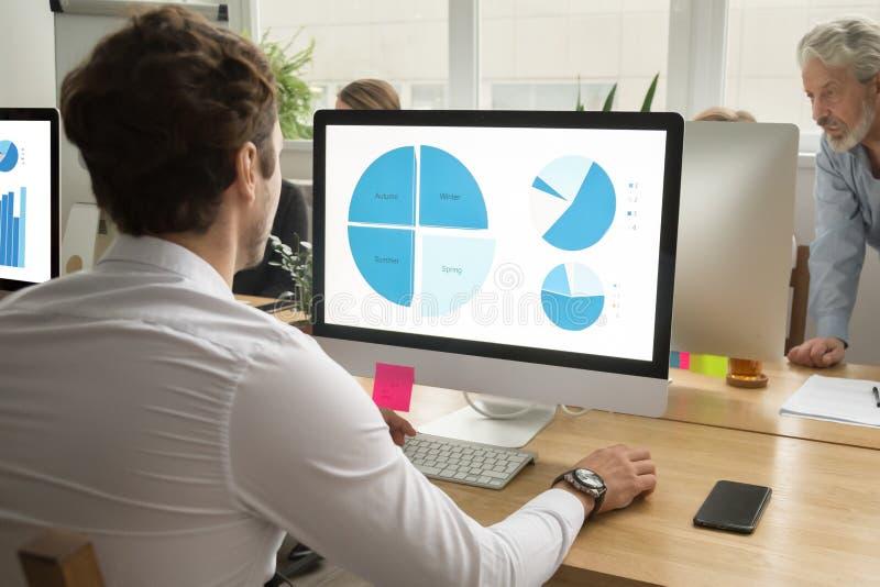 Młody pracownik używa komputer analizuje dane, statystyki analysi fotografia royalty free