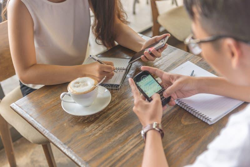 Młody pracownik używa smartphone i pisać notatce obraz stock