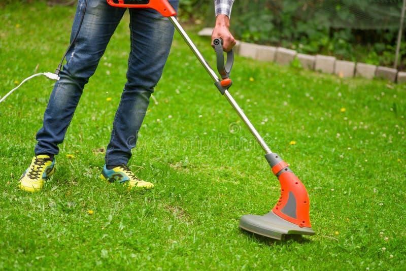 Młody pracownik z smyczkowego gazon drobiażdżarki kosiarza tnącą trawą w zamazanym natury tle fotografia royalty free