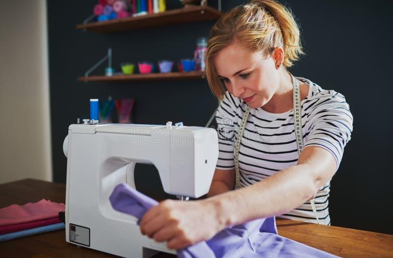Młody projektant mody używa szwalną maszynę zdjęcia stock