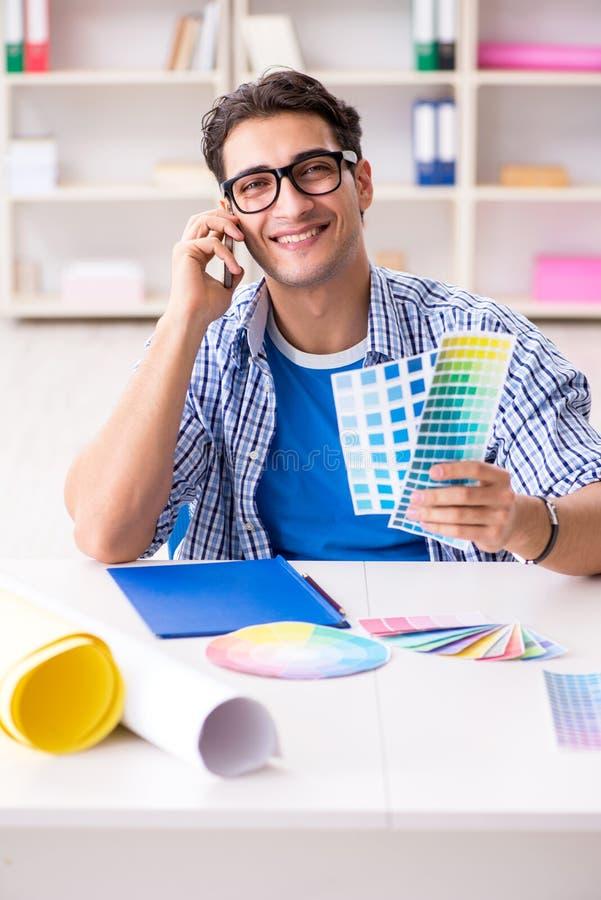 Młody projektant pracuje na nowym projekcie i wybiera colours zdjęcia stock