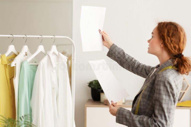 Młody projektant Sprawdza nakreślenia Na papierach I Porównuje zdjęcie stock
