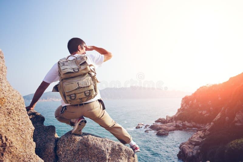 Młody przygoda mężczyzna obsiadanie na skałach nad ocean zdjęcie royalty free